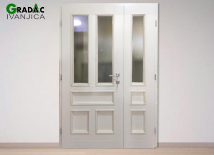 Dvokrilna bela ulazna drvena vrata, u gornjoj polovini peskareno staklo, u donjem delu drveni paneli, pogled sa unutrašnje strane